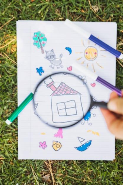Kinderzeichnung durch vergrößerungsglas über grünem gras Kostenlose Fotos