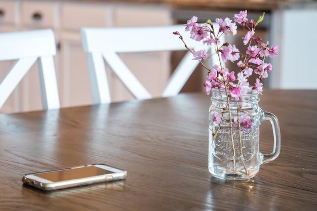 Kirschblüten und zweige in einem glas wasser auf dem tisch unter den lichtern Kostenlose Fotos