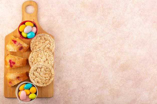Kirschkuchenscheiben einer draufsicht mit bonbons und keksen auf dem rosa schreibtischkuchen-kekszucker Kostenlose Fotos
