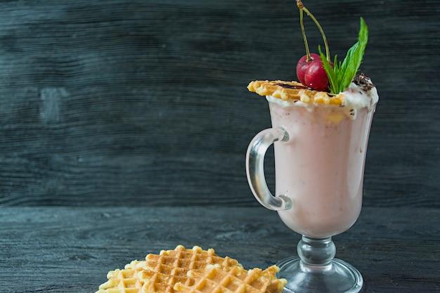 Kirschmilchshake mit eis und schlagsahne, marshmallows, keksen, waffeln, serviert in einer glasschale. Premium Fotos