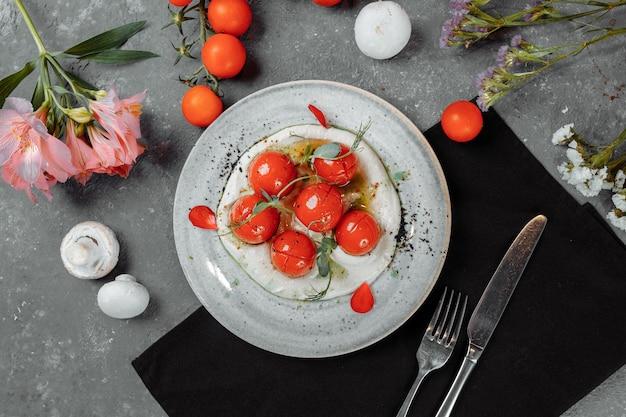 Kirschtomaten mit tofu-mousse auf einem teller. platz für die inschrift. Premium Fotos
