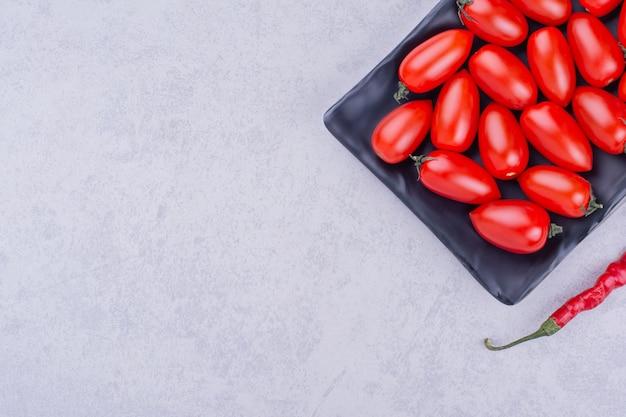 Kirschtomaten und roter chili in einer schwarzen platte. Kostenlose Fotos