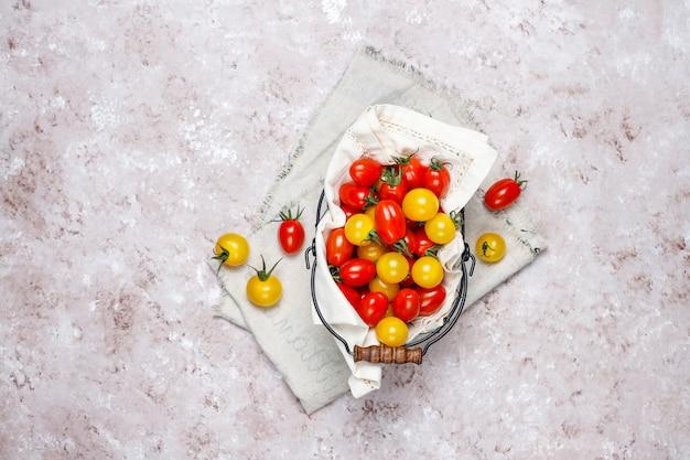 Kirschtomaten von verschiedenen farb-, gelben und rotenkirschtomaten in einem korb auf hellem hintergrund Kostenlose Fotos