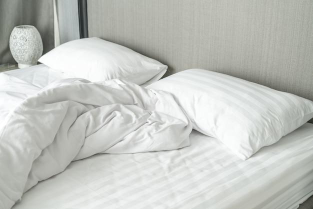 Kissen auf dem bett und mit falten chaotisch decke im schlafzimmer Premium Fotos