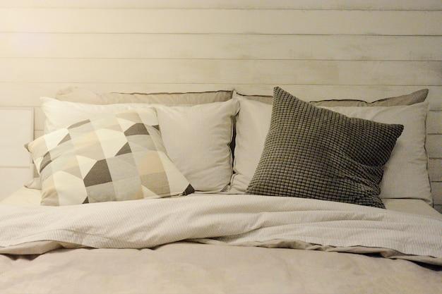 Kissen und decke auf bett im weinlese-hölzernen schlafzimmer mit der beleuchtung der oberen linken seite. Premium Fotos