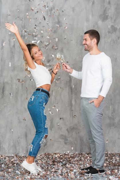 Klappernde gläser der paare mit champagner Kostenlose Fotos