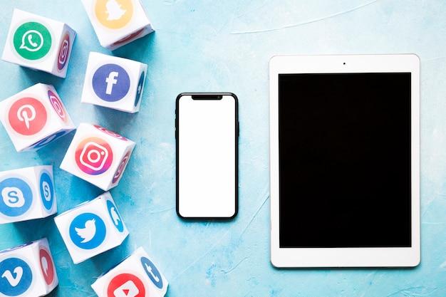 Klare social media-blöcke mit mobiltelefon und digitaler tablette auf blau malten wand Kostenlose Fotos