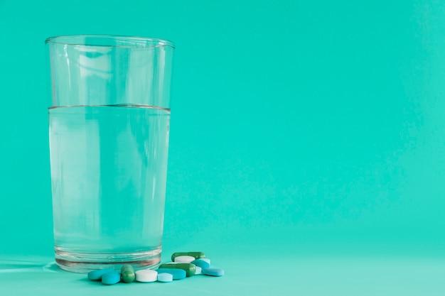 Klares glas wasser mit pillen auf türkishintergrund Kostenlose Fotos