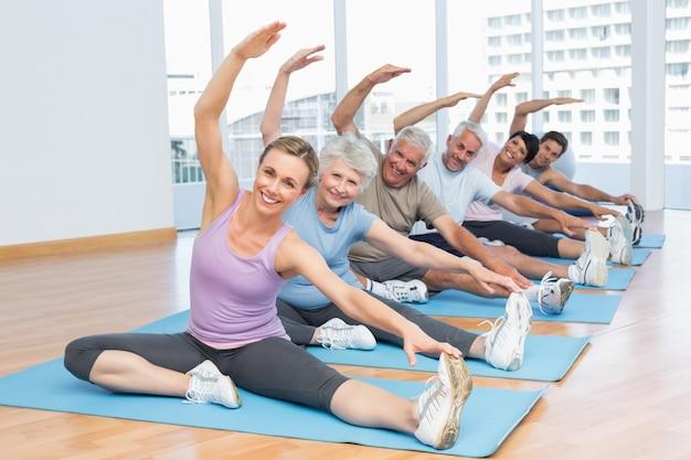Klasse, die hände an der yogaklasse ausdehnt Premium Fotos