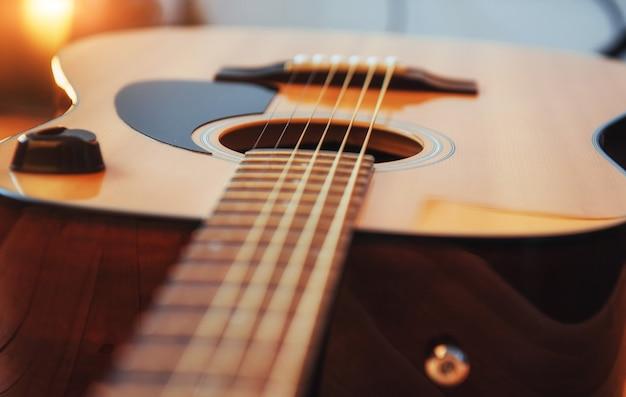 Klassische gitarre auf einem hellbraunen hintergrund Premium Fotos