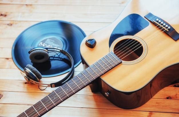 Klassische gitarre mit kopfhörern auf einem hölzernen hintergrund Premium Fotos