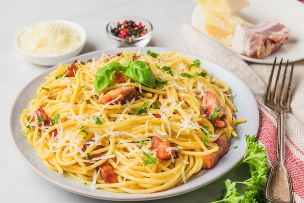 Klassische hausgemachte italienische pasta carbonara mit speck, eiern, parmesan und petersilie in einem teller mit gabel Premium Fotos
