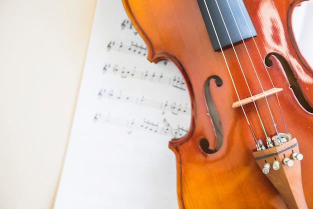 Klassische hölzerne violinsaite auf musiknote Kostenlose Fotos