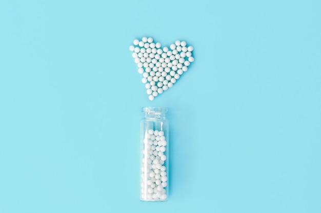Klassische homöopathiekügelchen in form von herz- und weinleseglasflaschen auf blauem hintergrund Premium Fotos