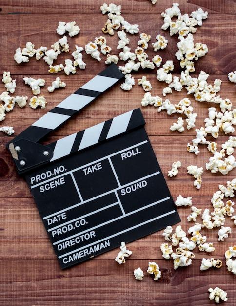 Klassische klappe und popcorn der weinlese auf braunem holztisch Premium Fotos