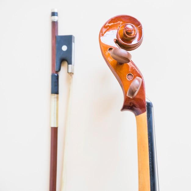 Klassische musikalische violine und bogen gegen weißen hintergrund Kostenlose Fotos