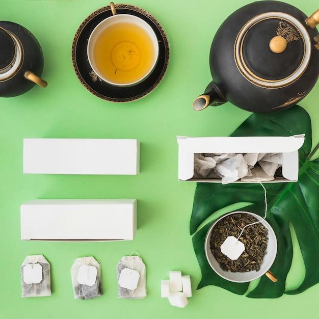 Klassischer asiatischer teesatz mit kräuterteebeutel auf grünem hintergrund Kostenlose Fotos