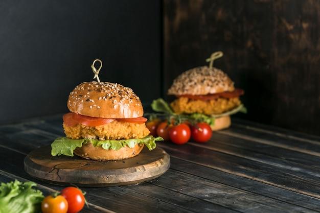 Klassischer burger mit hühnchen in einem brötchen mit sesam-tomaten, salat und senfsauce. Premium Fotos
