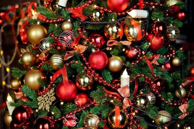 Klassischer grüner weihnachtsbaum mit blinkender girlande im dunklen raum. weihnachtsinnenraum Premium Fotos
