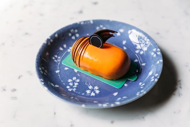 Klassischer thailändischer tee-mousses-kuchen verziert mit schokolade in der blauen platte auf marmortischplatte. Premium Fotos