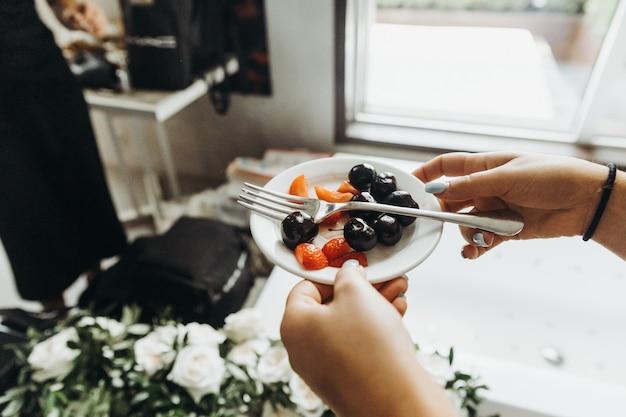 Klassisches bankett. frau hält kleine platte mit früchten in ihrem a Kostenlose Fotos