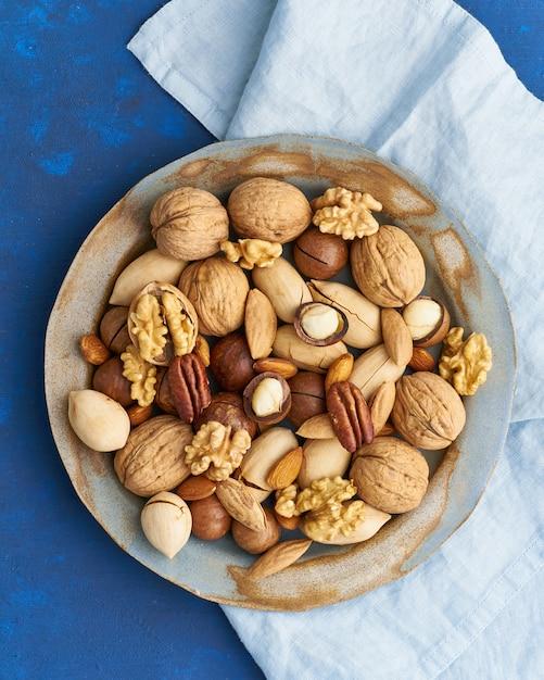 Klassisches blau in lebensmitteln. mischung von nüssen auf platte - walnuss, mandeln, pekannüsse, macadamia und messer Premium Fotos