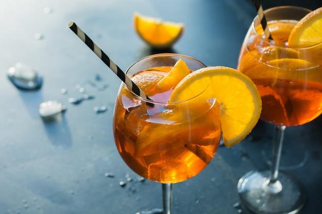 Klassisches italienisches aperol spritz cocktail auf dunkelheit. Premium Fotos