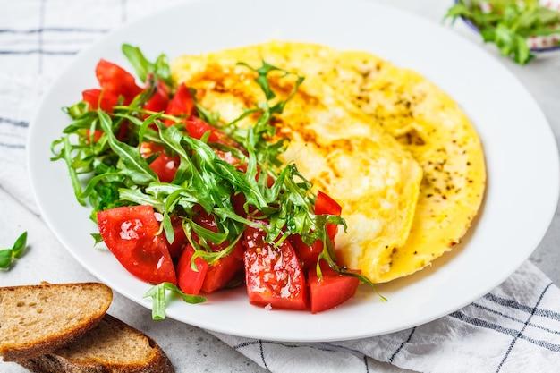 Klassisches omelett mit käse-tomaten-salat auf einem weißen teller. Premium Fotos