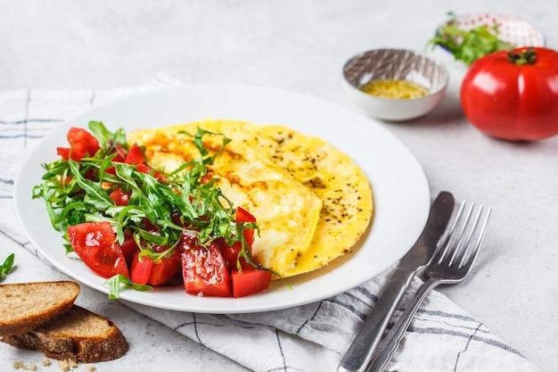 Klassisches omelett mit käse- und tomatensalat auf weißer platte. Premium Fotos