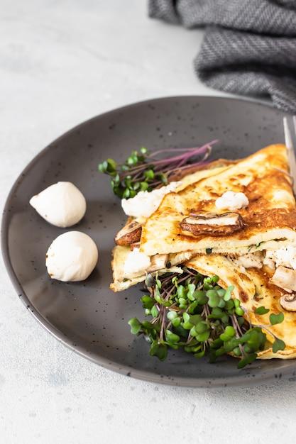 Klassisches omelett mit pilzen, mozzarella und mikrogrün. frühstück. Premium Fotos