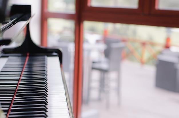 Klavier mit unschärfefensterhintergrund Premium Fotos