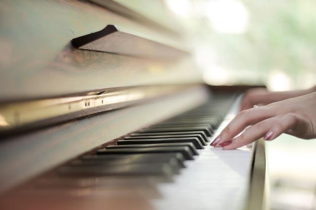 Klaviertastatur mit den weiblichen händen, die auf ihr spielen Premium Fotos