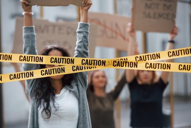 Klebeband, das die augen des mädchens bedeckt. eine gruppe feministischer frauen protestiert im freien für ihre rechte Kostenlose Fotos