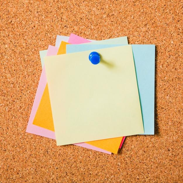 Klebrige postanmerkungen der verschiedenen farben mit druckbolzen auf korkenbrett Kostenlose Fotos
