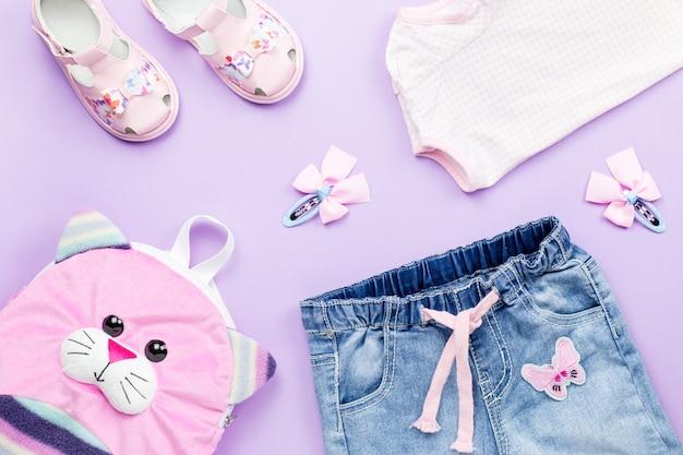 Kleiderkollektion flach lag mit t-shirt, jeans, sandalen, rucksack auf pastell Premium Fotos