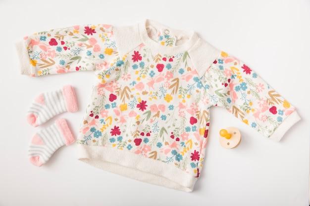 Kleidung und socken des babys mit dem friedensstifter lokalisiert auf weißem hintergrund Kostenlose Fotos
