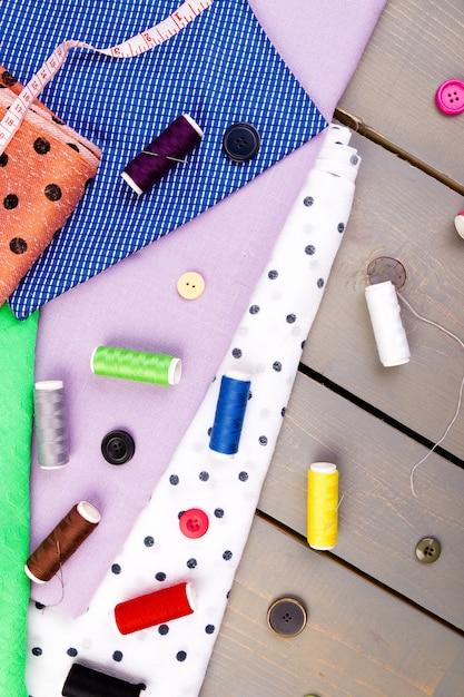 Kleidungsstücke zum nähen. knöpfe, garn- und stoffspulen nähen. ansicht von oben. Premium Fotos