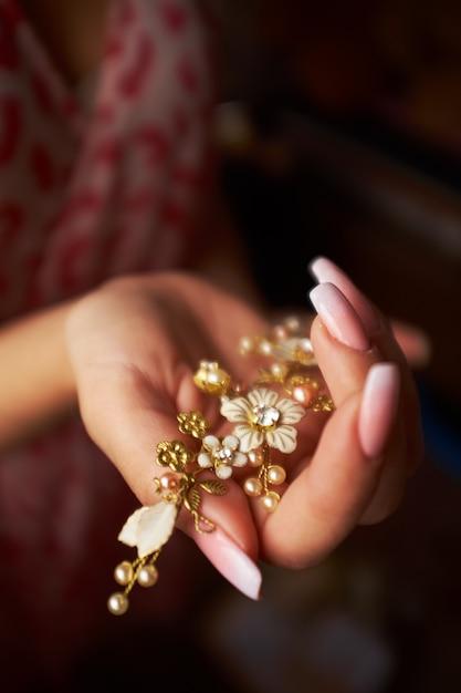 Klein in form von goldenen haarnadel der blumen in der hand eines mädchens Premium Fotos