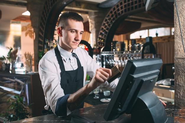 Kleinbetrieb-, leute- und servicekonzept - glücklicher mann oder kellner im schutzblech am zähler mit der geldkassette, die an der bar oder an der kaffeestube arbeitet Premium Fotos