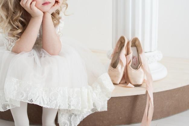 Kleine ballerina im weißen kleid, das nahe bei großen spitzenschuhen sitzt Premium Fotos