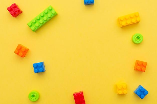 Kleine blöcke des plastikkonstruktors auf gelbem hintergrund, flache lage, draufsicht, platz für text Premium Fotos
