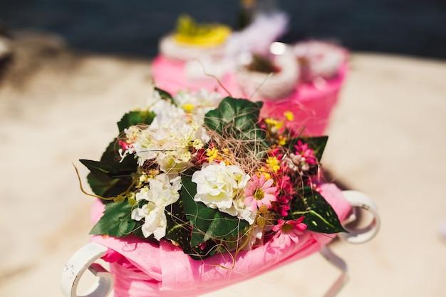 Kleine Blumensträuße von rosa und weißen Feldblumen liegen auf einer ...