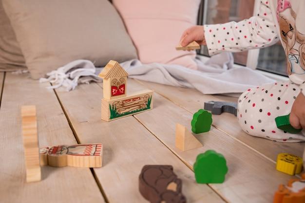 Kleine bunte hölzerne spielzeugformen und -bausteine auf massivholzboden mädchenspiel mit einem hölzernen satz in ihrem kinderzimmer auf dem boden. bunte blöcke auf dem boden. Premium Fotos