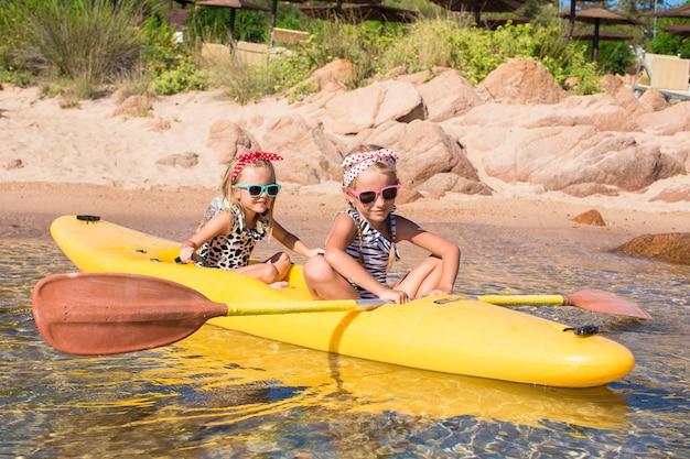 Kleine entzückende mädchen, die das kayak fahren im klaren türkisfarbenen wasser genießen Premium Fotos