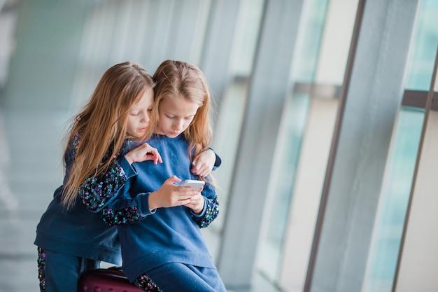 Kleine entzückende mädchen im flughafen, der auf das verschalen wartet und mit laptop spielt Premium Fotos