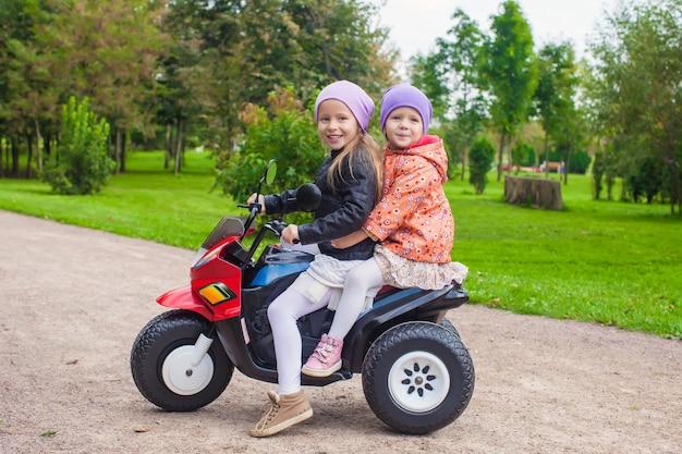 Kleine entzückende schwestern, die auf spielzeugmotorrad im grünen park sitzen Premium Fotos
