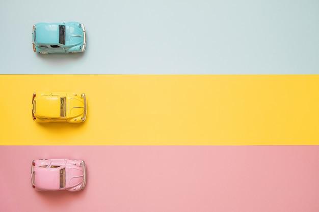 Kleine farbspielzeugautos am anfang auf einem gelb, einem rosa und einem blau Premium Fotos