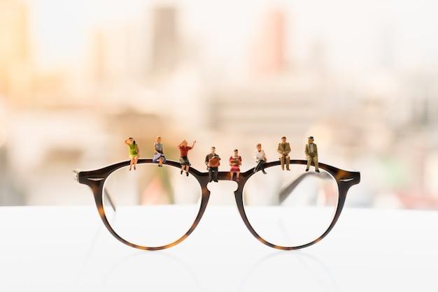 Kleine figur sitzt und wartet auf brille. Premium Fotos