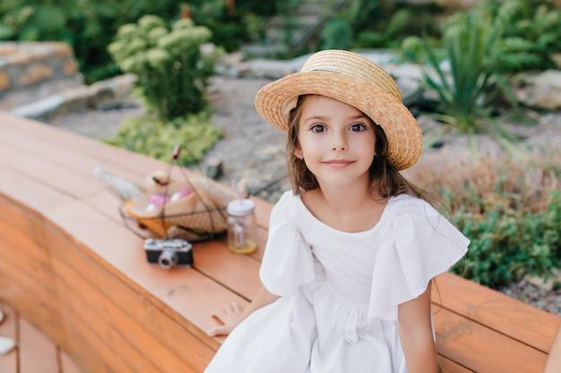 Kleine gebräunte dame im weinlesestrohhut, der auf hölzerner bank mit korb für picknick und kamera sitzt. außenporträt des dunkeläugigen mädchens trägt weißes kleid, das aufwirft Kostenlose Fotos