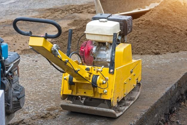 Kleine gelbe manuelle technik zum verlegen von asphalt. Premium Fotos